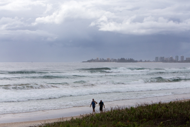 Some morning walkers enjoying the solitude and the angry clouds looming over Coolangatta..